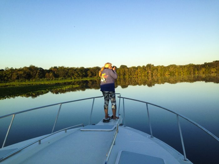 Kathy Passmore on the front of the Mon Ami at dawn, cruising down the St. John's River.