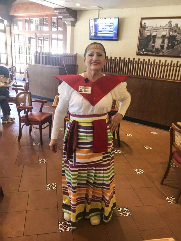 A waitress dressed in traditional Mexican garb